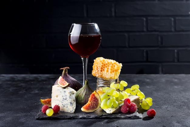 Raisin, fromage, figues et miel avec un verre de rouge sur un fond de pierre noir, espace de copie