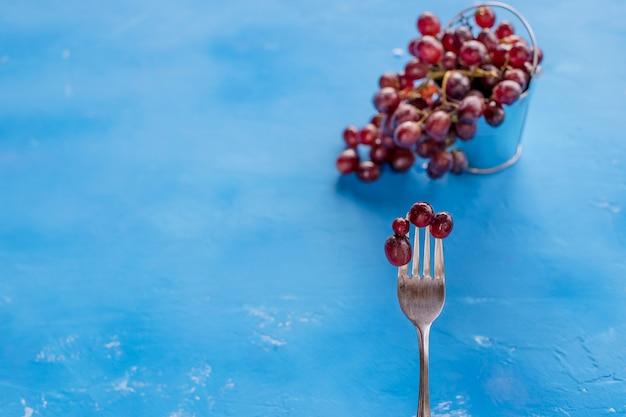 Raisin rouge frais avec une goutte d'eau isolée sur fond bleu