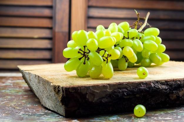 Raisin vert juteux sur une planche de bois rustique