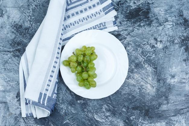 Raisins blancs à plat dans une assiette blanche avec une serviette de cuisine sur fond de marbre bleu foncé. horizontal