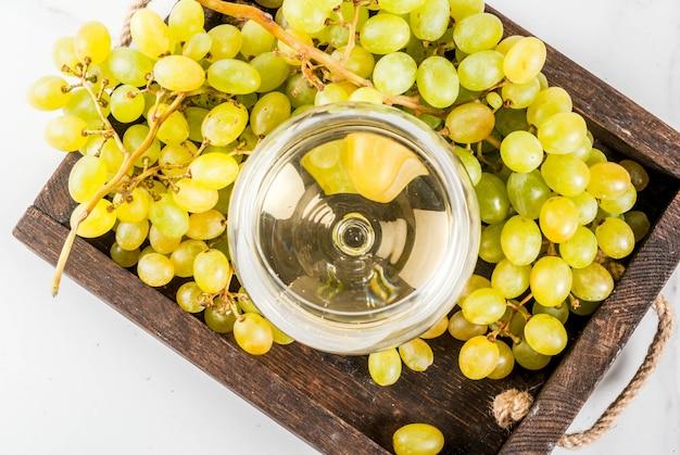Raisins blancs et vin blanc dans un verre, dans un plateau en bois. vue de dessus du fond
