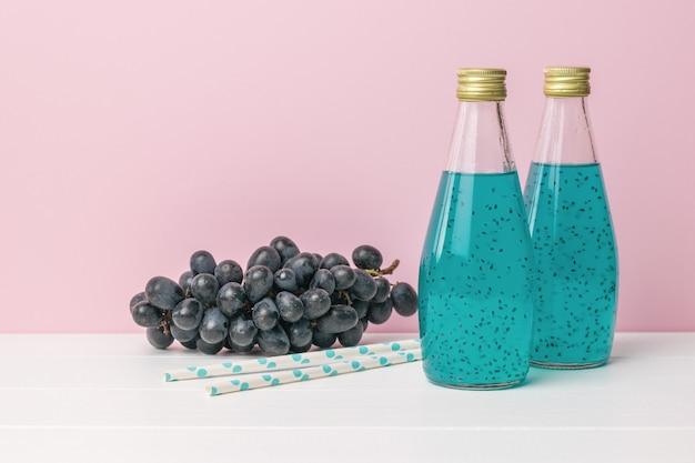 Raisins bleu foncé et deux bouteilles d'un cocktail avec des graines de basilic sur une surface rose
