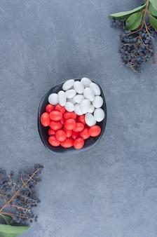 Des raisins et un bol de gommes, sur le fond de marbre.