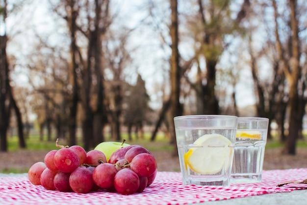 Des raisins à côté de verres avec de l'eau et du citron