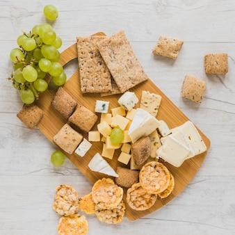 Des raisins, des craquelins, du pain croquant et des blocs de fromage sur le bureau en bois