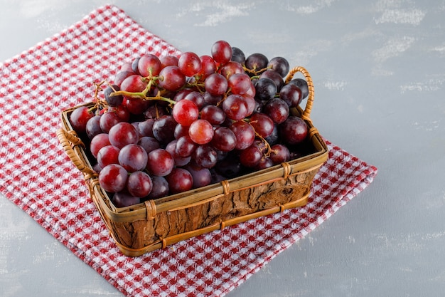 Raisins dans un panier sur toile de pique-nique et plâtre. vue grand angle.