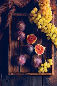 Raisins frais et figues sur une vieille surface en bois dans un style rétro