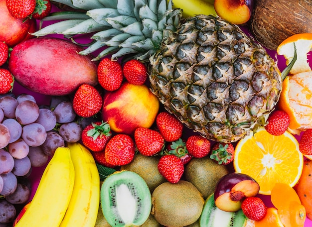 Les raisins; des fraises; ananas; kiwi; abricot; banane et ananas entier