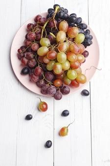 Raisins juteux mûrs sur une plaque sur un bois blanc. vue de dessus.