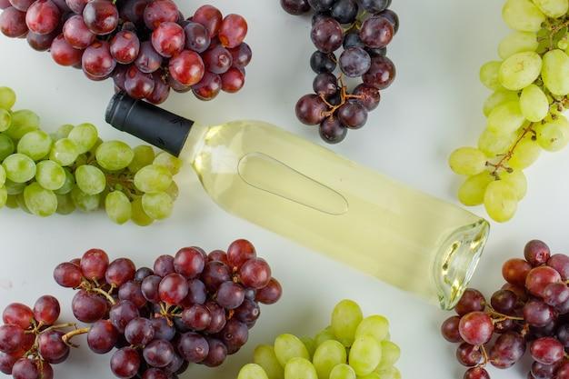 Raisins mûrs avec une bouteille de vin sur blanc,