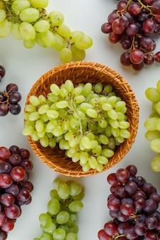 Raisins mûrs dans un panier en osier sur fond blanc.