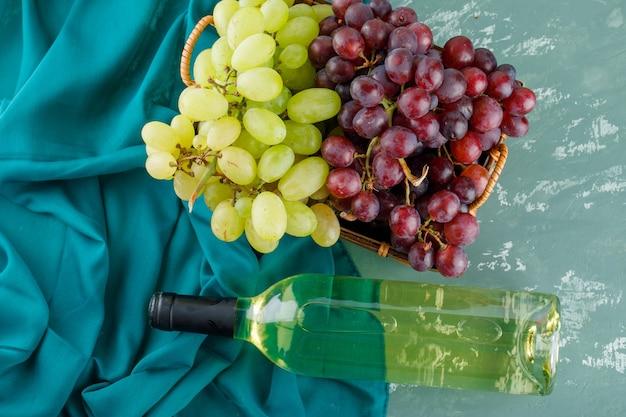 Raisins mûrs avec du vin dans un panier sur plâtre et textile,