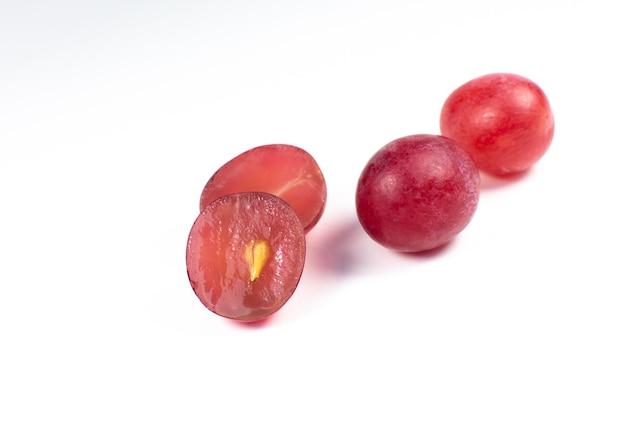Raisins mûrs violets coupés en deux sur fond blanc. gros plan photo. fruits écologiques pour les végétaliens. vitamines.