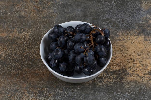 Raisins noirs frais dans un bol blanc.
