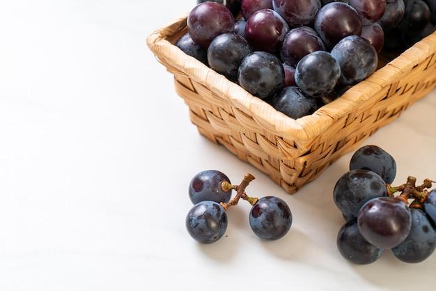 Raisins noirs frais sur fond blanc
