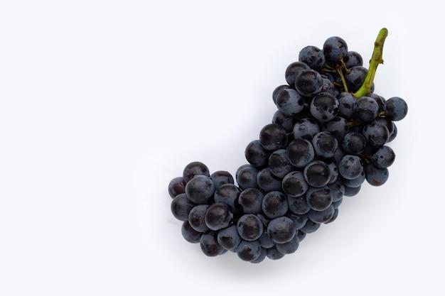 Raisins noirs frais sur fond blanc.