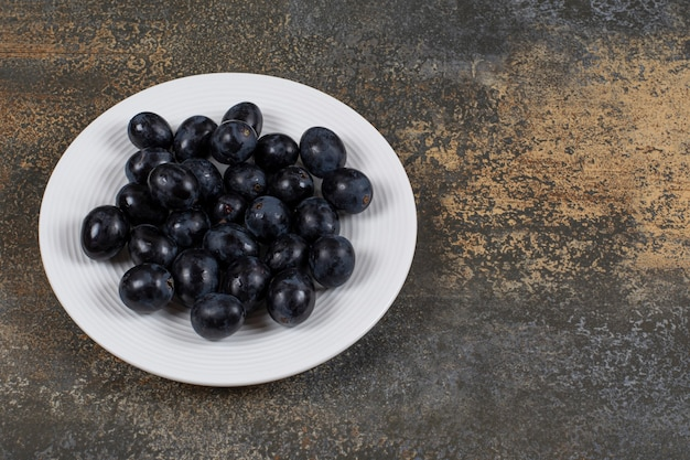 Raisins noirs frais sur plaque blanche.