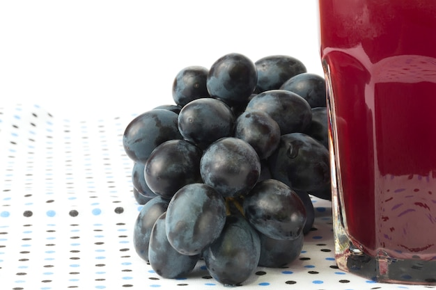 Raisins noirs isolé sur fond blanc verre de jus