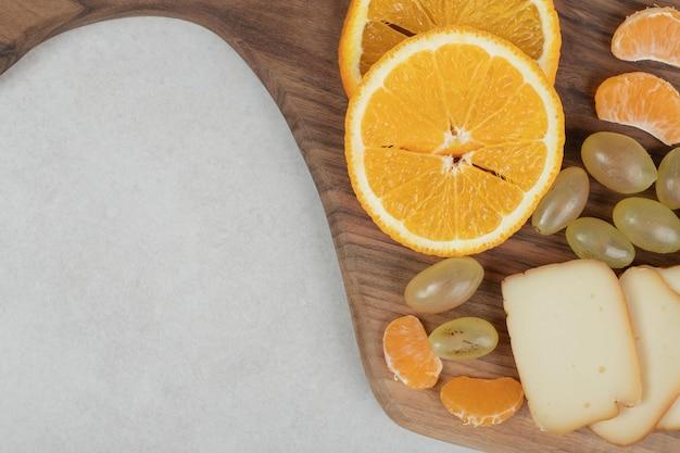 Raisins, oranges, mandarines et fromage sur planche de bois.