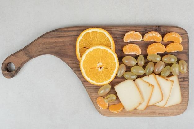 Raisins, oranges, mandarines et fromage sur planche de bois