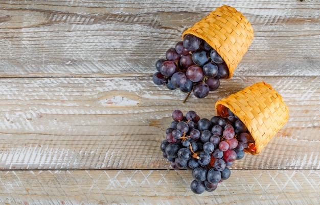 Raisins rouge foncé dans des paniers en osier sur fond de bois, pose à plat.