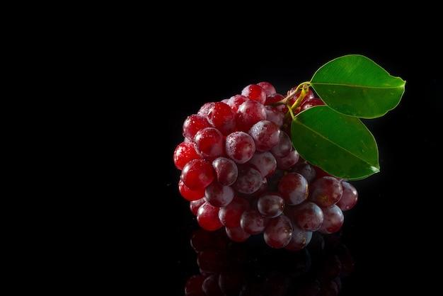 Raisins rouges sur acrylique noir.