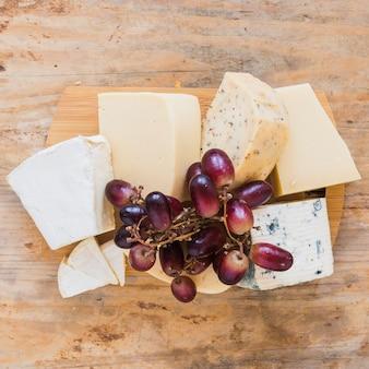 Raisins rouges sur les blocs de fromage sur planche de bois