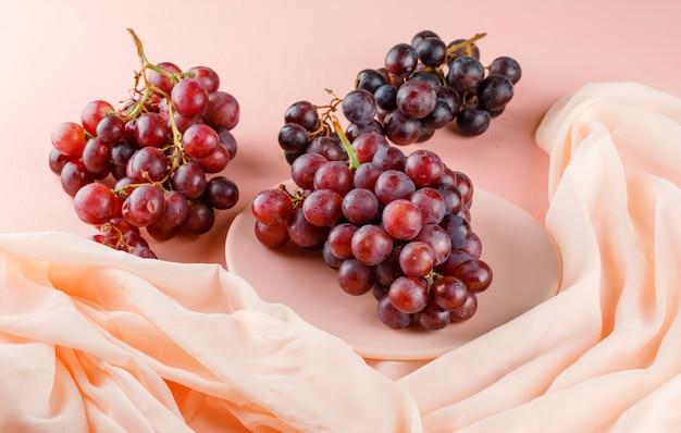 Raisins rouges dans une assiette sur rose et textile. vue grand angle.