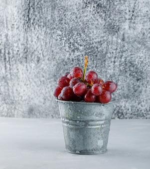 Raisins rouges dans un mini seau sur plâtre et grungy.