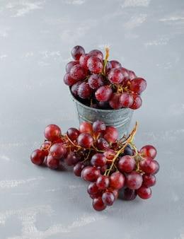 Raisins rouges dans un mini seau sur un plâtre. vue grand angle.
