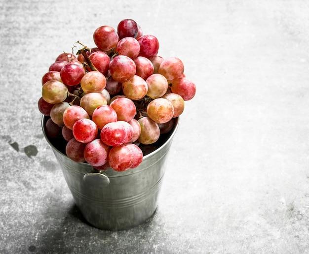 Raisins rouges dans un seau sur table en pierre.