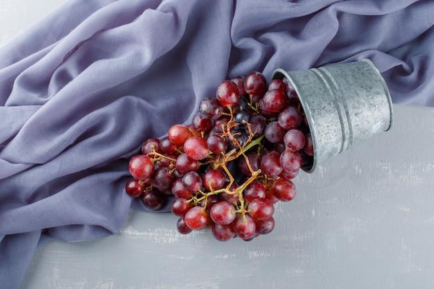 Raisins rouges épars d'un mini seau sur du plâtre et du textile,
