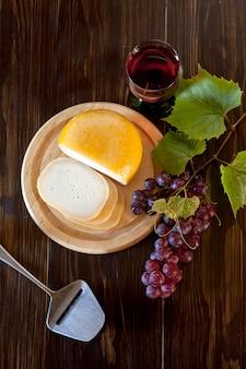 Raisins rouges avec des feuilles, verre de vin et fromage frais sur bois rustique. vue de dessus, gros plan.