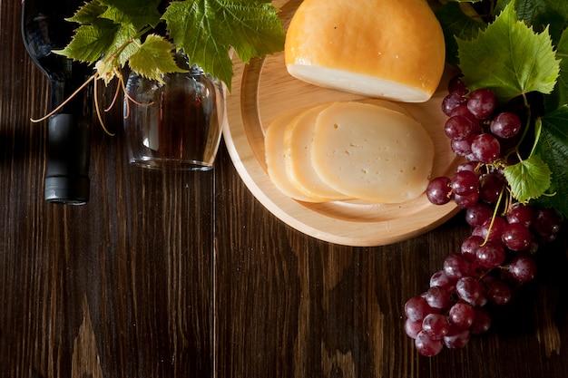 Raisins rouges avec des feuilles, verre de vin et fromage frais. vue de dessus, gros plan.
