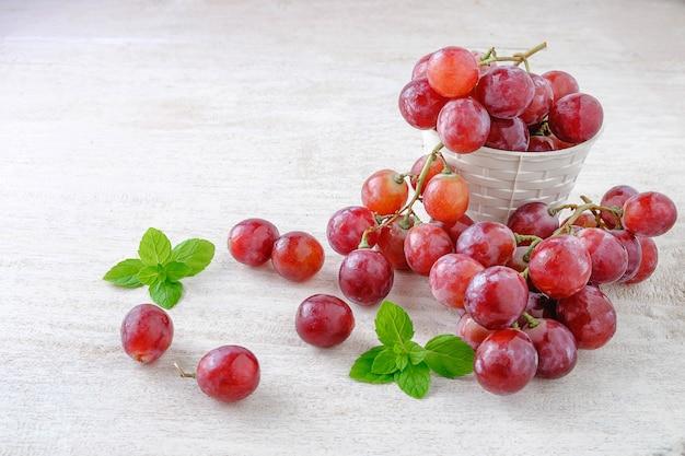 Raisins rouges frais dans un panier sur un fond blanc.