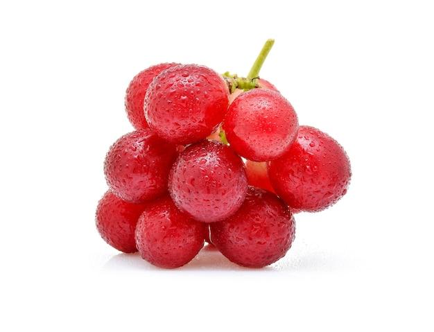 Raisins rouges avec goutte d'eau isolé sur fond blanc.