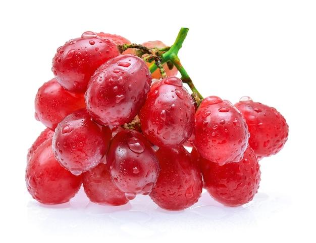 Raisins rouges avec des gouttes d'eau isolés sur fond blanc.