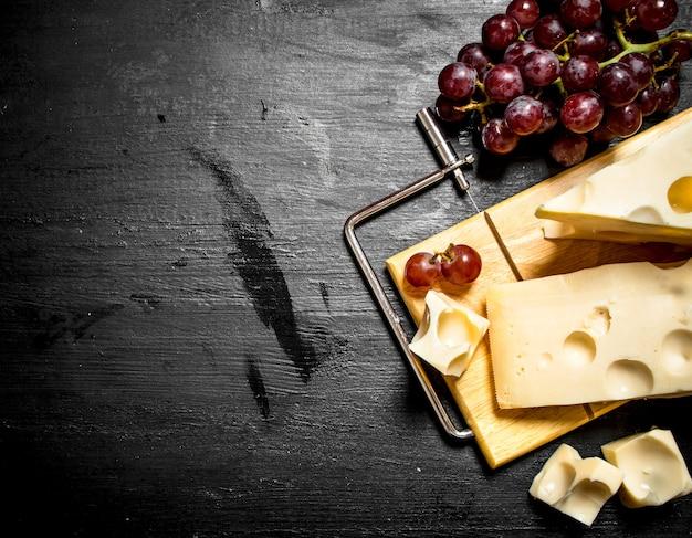 Raisins rouges et morceaux de fromage sur table en bois noir.
