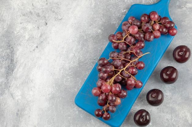 Raisins rouges sur une planche à découper bleue avec des prunes fraîches sur une surface en marbre.