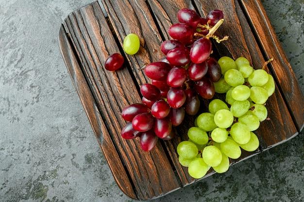 Raisins rouges et verts sur une planche de bois