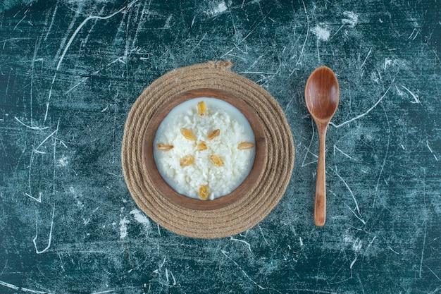 Raisins secs sur un bol de riz au lait à côté d'une cuillère, sur la table bleue.