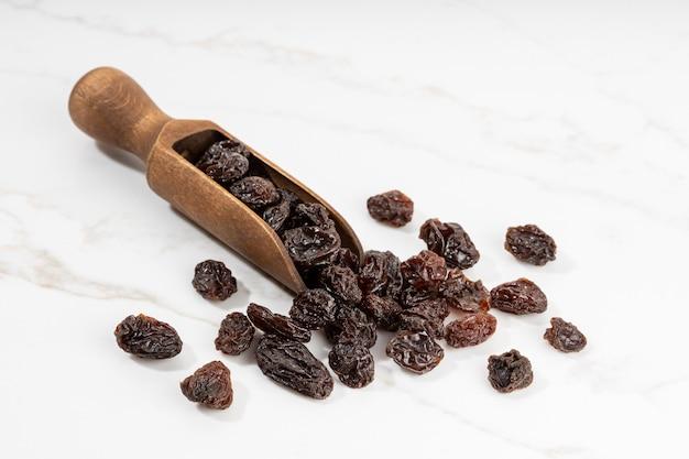 Raisins secs et cuillère isolés sur une surface en marbre blanc. raisin séché. copier l'espace