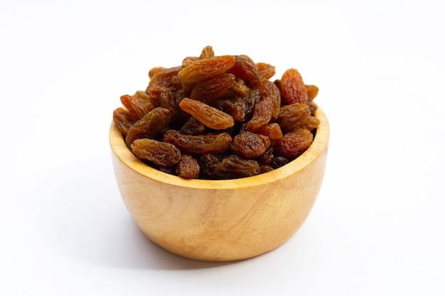 Raisins secs dans un bol en bois sur fond blanc