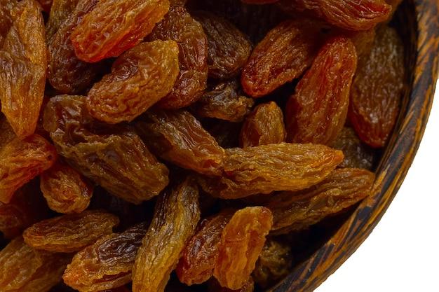 Raisins secs dans un bol en bois sur fond blanc.