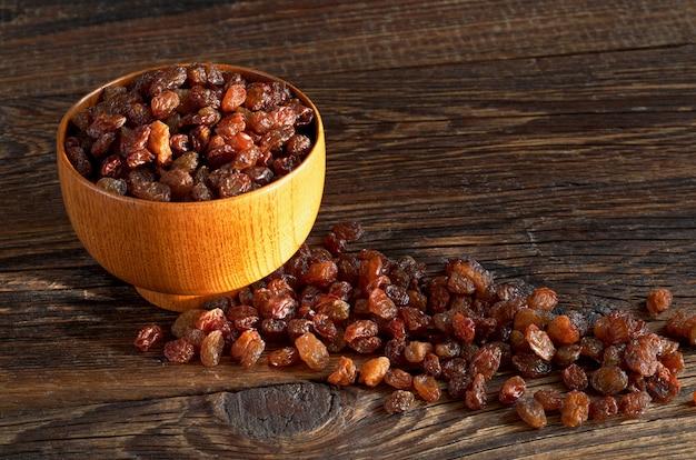 Raisins secs dans le bol sur la vieille table en bois au soleil