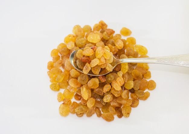 Raisins secs isolés sur fond blanc. une cuillère à raisins secs.