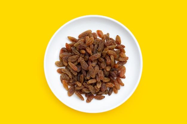 Raisins secs en plaque blanche sur fond jaune