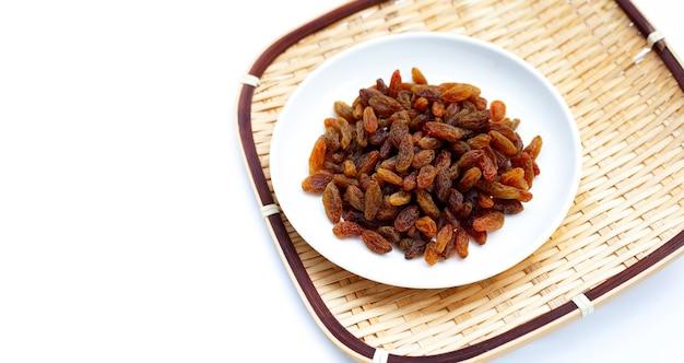 Raisins secs en plaque sur fond blanc