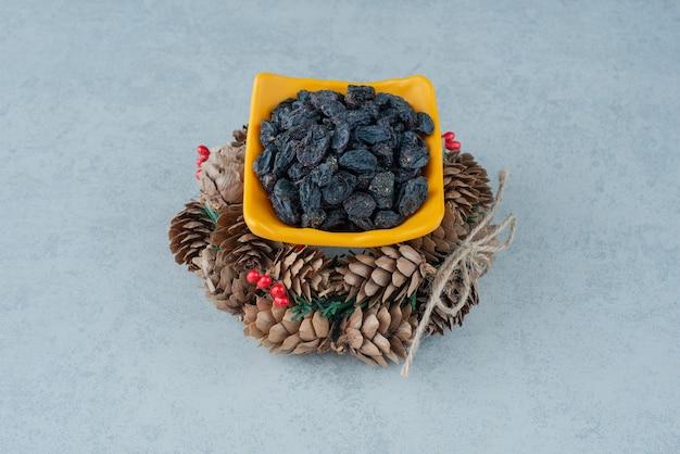 Raisins secs sains avec guirlande de noël de pommes de pin. photo de haute qualité