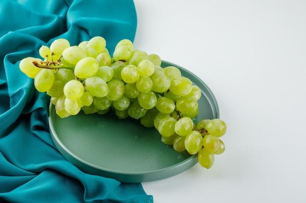 Raisins verts dans une assiette sur blanc et textile, vue grand angle.